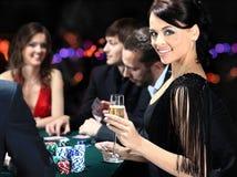 Spelare som sitter runt om en tabell på en kasino Royaltyfri Fotografi
