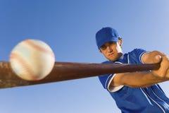 Spelare som slår bollen med baseballslagträet arkivfoto