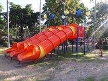 Spelaren av barn är det trevägs av den röda glidaren arkivfoton