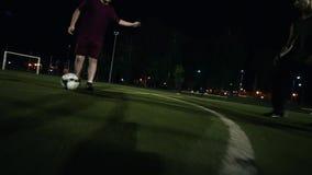 Spelaren i vita gymnastikskor gör överföringen av bollen till en annan spelare som kör med bollen och bryter i väg från arkivfilmer