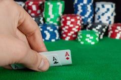 Spelaren kontrollerar hans hand, två överdängare in, fokusen på kort Royaltyfria Bilder