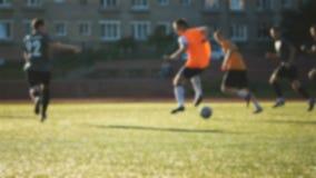 Spelaren och hans lag anfaller, den amatörmässiga fotbollleken på den lilla stadion i ultrarapid stock video