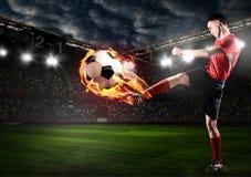 spelaren sparkar bollen Arkivbilder