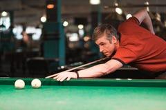 Spelaretagandeen siktar på bollen i biljard Royaltyfri Fotografi