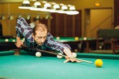 Spelaretagandeen siktar på bollen i biljard Arkivfoton