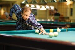 Spelaretagandeen siktar på bollen i biljard Fotografering för Bildbyråer