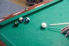 Spelaretagandeen siktar på bollen i biljard royaltyfria foton