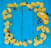 Spelcontrolemechanisme, spaanders en suikergoed op een blauwe houten achtergrond Stock Fotografie