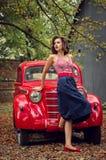 Speld-op meisje het stellen op een rode Russische retro autoachtergrond Speelse geinteresseerd ziet opzij wordt gegoten eruit royalty-vrije stock afbeelding