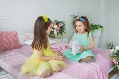 Spelen de mooie meisjes in gele en turkooise kleding op een bed in een studio royalty-vrije stock afbeeldingen