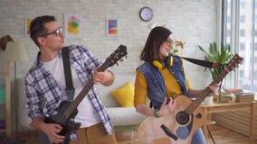 Spelen de portret jonge vrouw en een jonge man emotioneel gitaren en dans stock footage