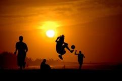 Spelen footbal bij de zonsondergang op het strand Stock Afbeeldingen