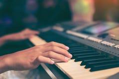Spelend het pianotoetsenbord dicht omhoog, Bebouwde handen van jong geitje het spelen piano in het klaslokaal royalty-vrije stock fotografie