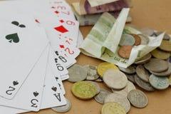 Spelenkaarten en geld in verschillende munt Concept het gokken, verslaving, online Stock Afbeeldingen