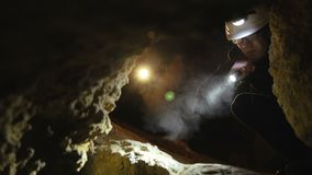 The speleologist finds the dangerous passage in the cave and starts to go. 4K.  stock footage