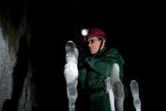 Speleologist in an ice cave. A caver in green overall and a helmet with a headlight among the ice stalagmites in the cave royalty free stock image