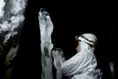 Speleologist in the ice cave. Speleologist takes a sample of the ice structure on the background of a darkness and rocky wall covered with large crystals of Royalty Free Stock Image