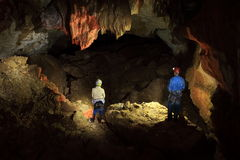 Speleologists in lightened cave Stock Images