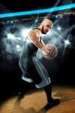 Speler in basketbal op de vloer met bal in handen die awa kijken Stock Foto