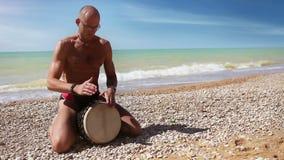 Speler van de Djembe sloeg de traditionele Trommel ritme op het eenzame strand stock footage