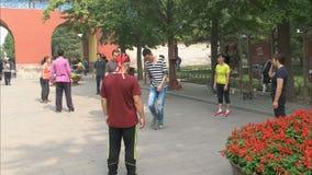 Spelers betrokken bij een spel van jianzi in Peking China stock footage