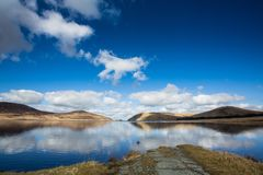 Spelga Dam, Northern Ireland. Landscape of clouds reflecting in calm waters at Spelga Dam in County Down, Northern Ireland with blue skies on sunny day royalty free stock photos