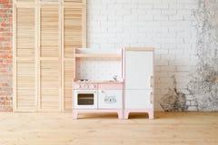 Spelkeuken voor kinderen Roze en witte houten stuk speelgoed keuken met gootsteen, oven en koelkast in lichte ruimte op witte bak stock afbeelding