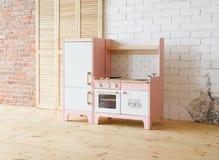 Spelkeuken voor kinderen Roze en witte houten stuk speelgoed keuken met gootsteen, oven en koelkast in lichte ruimte met houten v stock foto's