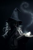 Spell book. Young witch with magic book posing over dark background Royalty Free Stock Photo