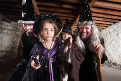 Spell Casting Family. Magician father and children casting spells in a basement Stock Image
