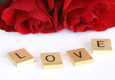 Spell It Out For Me. Letter tiles with red roses spell out a message of love Royalty Free Stock Photo