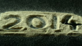 2014 spelled out in sand blowing away stock footage