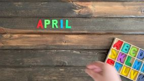 Overhead time lapse video of a child`s hand spelling out an April Fools Day message in colored block letters on a wooden stock footage