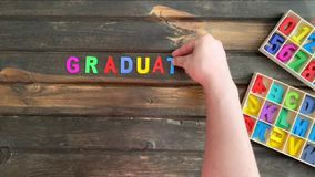 Overhead time lapse video of a child`s hand spelling out Graduation 2020 message in colored block letters on a wooden stock video