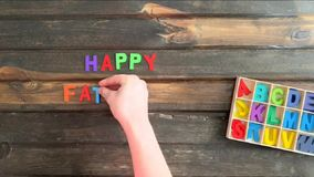 Overhead time lapse video of a child`s hand spelling out a Happy Fathers Day  message in colored block letters on a wooden stock video