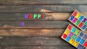 Overhead time lapse video of a child`s hand spelling out a happy holiday message in colored block letters on a wooden stock video footage