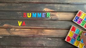 Overhead time lapse video of a child`s hand spelling out a happy summer vacation  message in colored block letters on a wooden stock video
