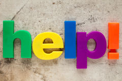 Spelling word HELP. Letter magnets spelling word HELP on dirty background royalty free stock photos
