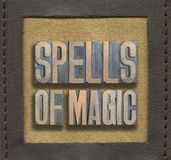 Spells of magic framed. Spells of magic phrase made from vintage wooden letterpress inside stitched leather frame Royalty Free Stock Photo