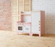Spelmeubilair voor kinderen Roze en witte houten stuk speelgoed keuken met gootsteen, oven en koelkast in lichte ruimte stock afbeeldingen