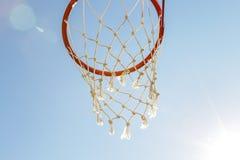 Spelsporten, competities Teamsporten, openluchtvrije tijd, actieve recreatie, vermaak Basketbalhoepel met netto tegen blauw royalty-vrije stock afbeelding