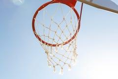 Spelsporten, competities Teamsporten, openluchtvrije tijd, actieve recreatie, vermaak Basketbalhoepel met netto tegen blauw royalty-vrije stock fotografie