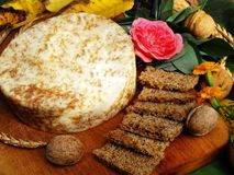 Spelt Bread with special cheese with nuts. On wooden board. Arrangement with food and flowers. Very healthy dish. Full of energy, vitamins and fibers. Super stock photo