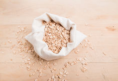 Spelt flakes in a cream fabric bag with a few flakes scattered on the wood Stock Photo