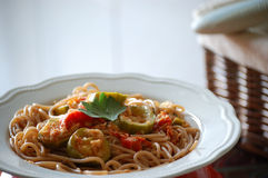 Spelt Pasta Dish. Spelt pasta with white fish, zucchini and tomato sauce Royalty Free Stock Image