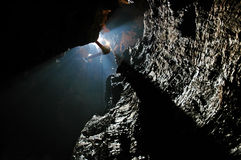 Spelunker abseiling in a cave. On a rope Royalty Free Stock Photography