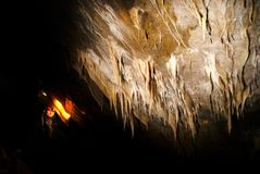 Spelunker admiring stalactites in a cave stock photography