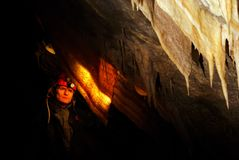 Spelunker admiring stalactites in a cave. Spelunker admiring stalactites in the cave Stock Photography
