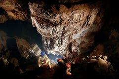Spelunker que admira las estalactitas hermosas en una cueva Fotos de archivo libres de regalías