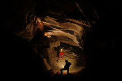 Spelunkers exploring an underground cave. Hall Stock Photo